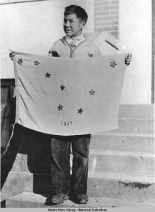 Benny Benson holding the Alaska flag