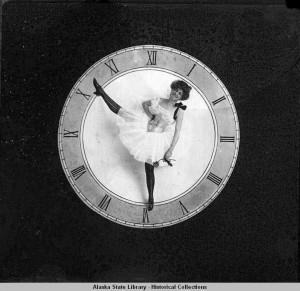 Clock face with tutu-clothed woman posing, toes pointing to 10:30. ASL-P226-723, William R. Norton Photographs, Alaska State Library-Historical Collections.