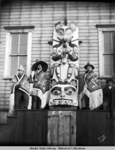 Men in regalia next to Panting Wolf carving, Sitka, Alaska, 1904. ASL-P57-020, Elbridge W. Merrill Photograph Collection, Alaska State Library-Historical Collections.