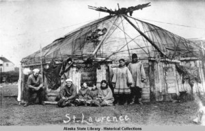 "St Lawrence Islanders pose with two sailors in white caps in front of a ""Chuckchi style"" house. ASL-P01-3198, Alaska State Library Photograph Collection, Alaska State Library-Historical Collections."
