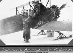 Joe Crosson on wing of plane and Arthur Johnson loading diptheria antitoxin for delivery to Barrow, Alaska, circa 1930. UAF-2003-63-31. Walter W. Hodge Papers, University of Alaska Fairbanks Archives.