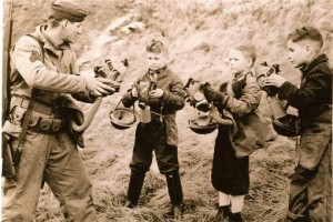A serviceman shows three youngsters how to put on a gas mask, Kodiak, Alaska, December 1942. P-713-1, Wilken Collection, Kodiak Historical Society.