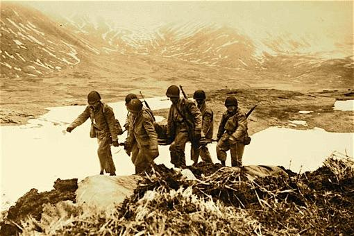 Men carrying a litter when American troops landed on Attu, Aleutian Island, May 11, 1943. UAF-1970-11-32, San Francisco Call-Bulletin, Aleutian Islands Photographs, University of Alaska Fairbanks Archives.