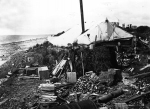 Living Off the Land: Using tundra for insulated walls and driftwood for heat, these guys are experienced residents of the golden beaches of Nome. How can you tell? Note the extremely tall smokestack built to extend out of a large winter snowdrift that will encompass their palace by February. Photo by Wilfred McDaniel from the Carrie M. McLain Memorial Museum Archives