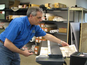 The 20 inch by 26 inch folio pages were disassembled and individually hand fed into a ColorTrac II scanner. Dave Dubois gently handles the pages going in and coming out. (Photograph byJ P Goforth)