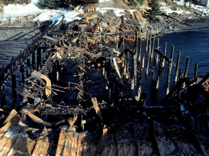 Glacier Bay Seafoods dock in Ouzinkie after the fire that destroyed it, 1975. Photo by Warren Good